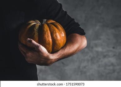 Hombre sujetando calabaza madura en manos sobre un fondo gris