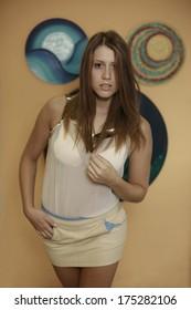 Bild eines schönen jungen Mädchens, das interessiert schaut und in die Kamera schaut und Ihre langen Haare korrigiert