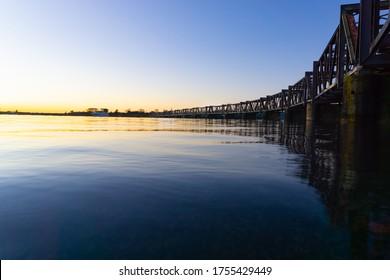 Las amplias líneas del histórico puente ferroviario de Tauranga con el amanecer a la izquierda proyectan tonos dorados en el horizonte del puerto, Nueva Zelanda.