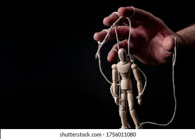 El empleador manipula al empleado, la manipulación emocional y obedece el concepto maestro con una mano siniestra tirando de los hilos de una marioneta con un contraste cambiante sobre fondo negro con espacio de copia