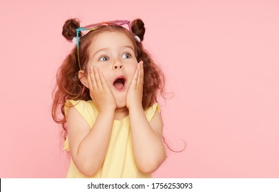 Portrait of surprised cute little toddler girl in sunglasses over pink background. Child model have fun and jump. Advertising childrens products