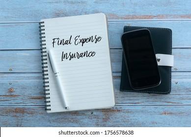 Vista superior del teléfono móvil, lápiz y cuaderno escrito con seguro de gastos finales sobre fondo de madera.