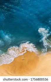 青い海、垂直方向の景色と美しい砂浜。トロピカルブルーオーシャンビーチヌサペニダバリインドネシアのドローンビュー。美しい波のある孤独な砂浜。インドネシアのビーチ。コピースペース