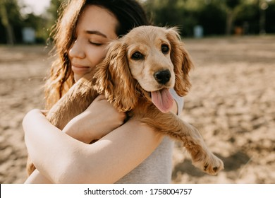 Young brunette woman holding and hugging her little dog, cocker spaniel breed puppy.