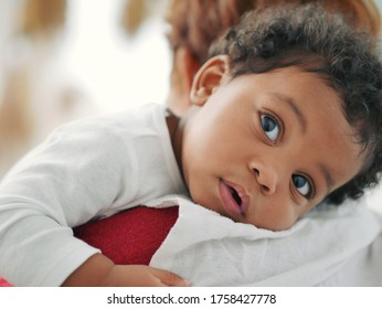African American child is sleeping on the shoulder of a mother who is holding her.