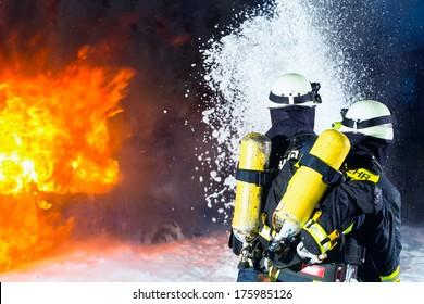 消防士-大きな炎を消している消防士、彼らは火の壁の前に保護服を着て立っています