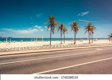 Palmen auf Ipanema Beach mit blauem Himmel, Rio de Janeiro, Brasilien. Berühmtes Bürgersteigmosaik vor dem Strand