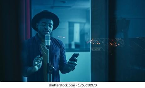 Portret van succesvolle jonge zwarte artiest, zanger, artiest zingt zijn hitnummer voor het nieuwe album. Stijlvolle hoed dragen, smartphone vasthouden en staan in de geluiddichte kamer van de muziekstudio.