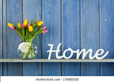 Home in white letters with colorful bouquet tulips in pink and yellow isolated on background