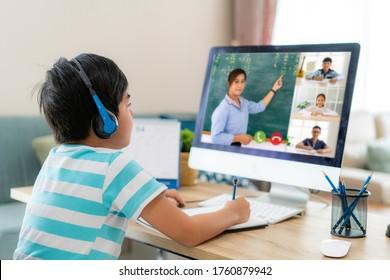 自宅の居間でコンピューターを使って教師やクラスメートとeラーニングを行うアジアの男子生徒のビデオ会議。ホームスクーリングと遠隔教育、オンライン、教育、インターネット。