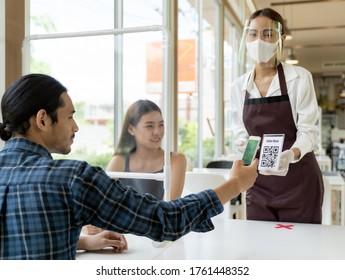 Cliente asiático escanea el menú en línea del código QR de la camarera con mascarilla y protector facial. El cliente se sentó en la mesa de distanciamiento social para un nuevo estilo de vida normal en un restaurante después de la pandemia del coronavirus covid-19