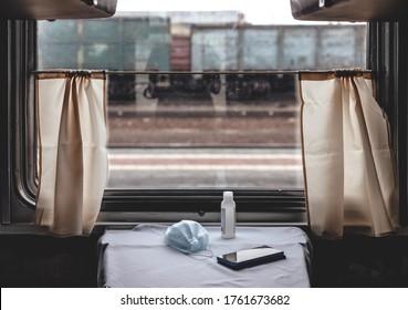 ロシアの長距離列車の内部。列車のコンパートメントの窓。テーブルの上の消毒剤、マスク、電話コロナウイルスパンデミック中COVID 19
