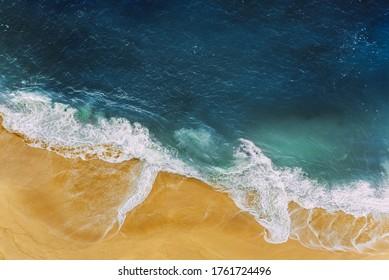 海岸、高さからの眺め。青い海と黄色い砂浜。鳥瞰図のある人けのないビーチ。海の波が砂浜を転がります。美しい海の風景。海、波、砂。コピースペース