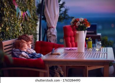 楽しんで、電話で漫画を見て、夏の夜に居心地の良い屋上パティオで時間を過ごすかわいい兄弟