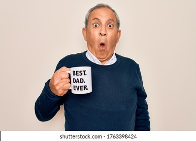 Senior man drinking cup of coffee with best dad ever message over white background scared in shock with a surprise face, afraid and excited with fear expression