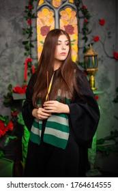 Una joven bruja con un manto negro con una varita mágica en sus manos conjura un hechizo mientras está de pie contra el telón de fondo de una ventana medieval.