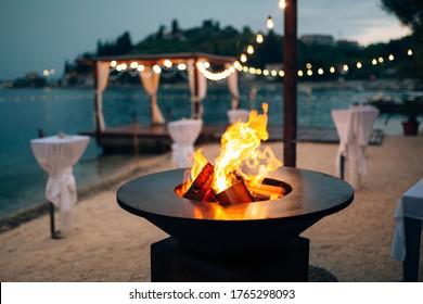 中に炎を入れてグリルします。ラウンドテーブル-調理面。ビーチで、花輪のある水辺の望楼の背景で、薄明かりの中で。