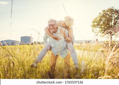 Starker älterer Mann, der seine lebenswichtige Frau ohne Rückenschmerzen huckepack trägt