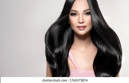 光沢のある黒とストレートの長い髪の美しいアジアのモデルの女の子。ケラチン矯正。髪のトリートメント、ケア、スパの手順。滑らかな髪型の中国の女の子