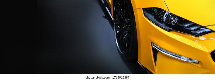 Vorderscheinwerfer des gelben modernen Autos auf schwarzem Hintergrund, Kopienraum