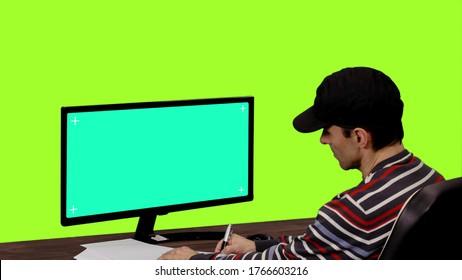 Programador informático escribiendo notas frente a maqueta en pantalla verde Chroma key