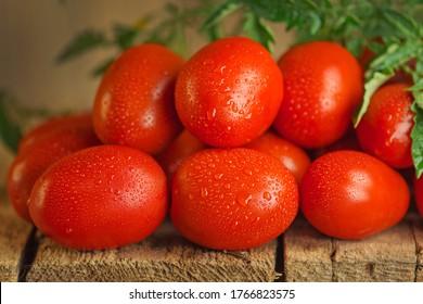 新鮮なオーガニックのジューシーなローマトマト。木製の背景に新鮮な熟したおいしいローマトマト