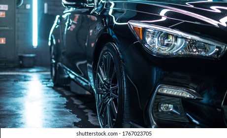 Nahaufnahme des Scheinwerferdetails des modernen Luxus-Sportwagens mit Reflexion auf roter Farbe nach dem Waschen & Wachs. Vorderansicht des Supersportwagens mit Backsteinmauer. Konzept der Autodetails und des Lackschutzhintergrunds.