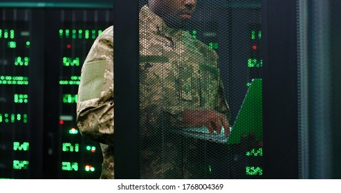 Close up of young African American military officer checking work of servers in analytic monioring center. Man with laptop computer control networking in dark room Cybersecurity in army concept.
