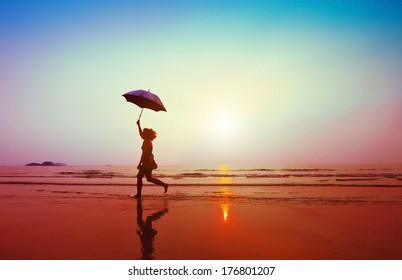 glückliche Frau, die mit Regenschirm am Strand springt