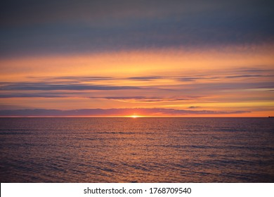 Sunset sky reflecting in the water, aerial view from the sandy shore. Setting sun. Abstract art, natural pattern. Baltic sea, Sweden. Idyllic seascape. Travel destinations, vacations concept