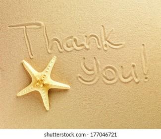 Las palabras Gracias están escritas sobre un fondo de arena y la estrella de mar yace cerca