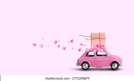 Roze retro auto met geschenkdoos op een dak met bloemen op roze achtergrond.