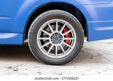 Elegante rueda de coche azul con pinza de freno roja y llanta de cinco tuercas. Soporte del sistema de frenos