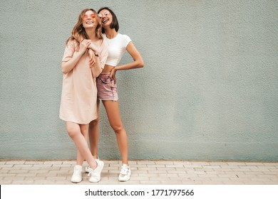 Zwei junge schöne lächelnde Hipster-Mädchen in den trendigen Sommerkleidern. Sexy sorglose Frauen, die auf Straßenhintergrund in der Sonnenbrille aufwerfen. Positive Models, die Spaß haben und sich umarmen