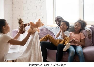 すべての家族は家の概念で週末に余暇面白い教育活動を楽しんでいます。アフリカの母親は、子供と夫のための演劇のパフォーマンスを示すハンドパペットマリオネットぬいぐるみを持っています