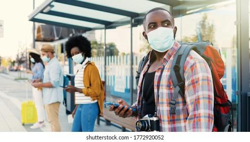 バス停に並んでいる医療用マスクの混血の若い男性と女性の人々。安全な社会的距離を保つ。輸送を待っている屋外のアフリカ系アメリカ人のスタイリッシュな男性観光客。観光客。