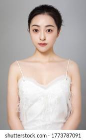 Aziatisch meisje dat wit kostuum op grijze achtergrond draagt