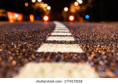 Carretera asfaltada que conduce a la ciudad por la noche. Enfoque selectivo. antecedentes