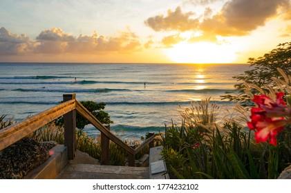 NAHAUFNAHME, LENS FLARE: Goldene Sonnenstrahlen am Abend scheinen auf einen Weg, der zu einem beliebten Surfstrand in Barbados führt. Die üppige Vegetation umgibt ein Treppenhaus, das zum Strand hinunterführt, wo Touristen bei Sonnenuntergang surfen.