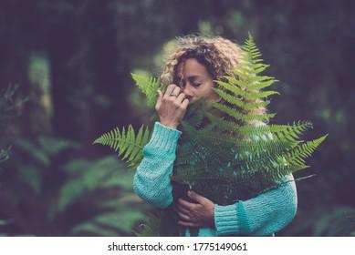 Rette den Planeten Erde und feiere den Tag der Erde mit einer erwachsenen Frau, die ein grünes Blatt im Waldwald umarmt und die Natur genießt - stoppe das Entwaldungskonzept mit Menschen, die die Natur lieben