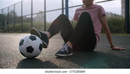 Junges kaukasisches Mädchen, das Fußballfähigkeiten und -tricks mit dem Fußball bei Sonnenuntergang in einem Spielplatz übt. Urban City Lifestyle Outdoor-Konzept