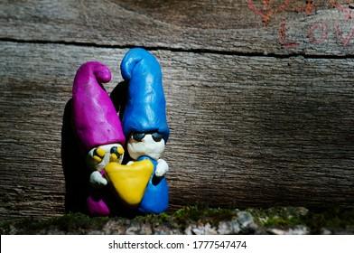 Zwei Gnome aus Ton, die ein Herz halten. Feenfiguren auf einem hölzernen Hintergrund.