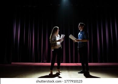 劇場でのリハーサル。男は学生女優に新公演の舞台での遊び方を説明する。背景の暗いホール。