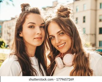 Nahaufnahmeporträt von zwei jungen schönen lächelnden Hipster-Frauen in den trendigen weißen Sommer-T-Shirt-Kleidern. Sexy sorglose Frauen, die auf Straßenhintergrund aufwerfen. Positive Modelle, die Kamera betrachten. Schönheitskonzept