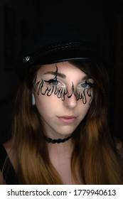 Modelo de maquillaje de ojos azules delineado flameado negro con boina negra mirando a la cámara sobre fondo oscuro