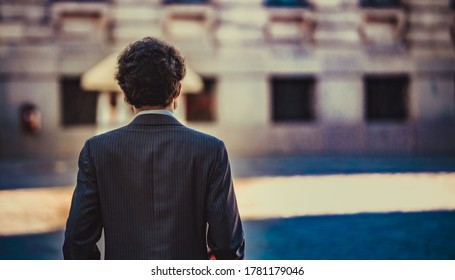 male portrait standing alone in the city. back view. Selective focus