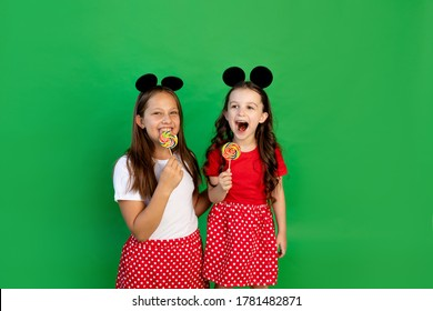 Cute little girls in red outfits and Mickey mouse ears on a green isolated background eat large lollipops. Space for text.the concept of the celebration and sales