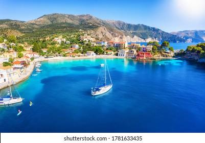 Schöne Aussicht auf das malerische Fischerdorf Assos, Kefalonia, Griechenland, mit Segelbooten, die über dem türkisfarbenen Meer festgemacht sind