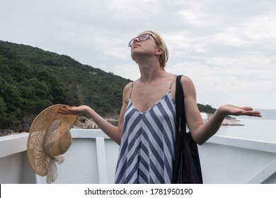 Disappointed female tourist on summer cruss ship vacation, standing on rain and looking angry at overcast cloudy sky. Allways take the weather with you on summer vacations.