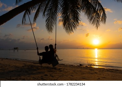 Silhouetted couple in love walks on the beach during sunset. Riding on a swing tied to a palm tree and watching the sun go down into the ocean.